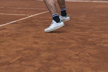 Details of the shoes of a tennis player during a match on a clay court