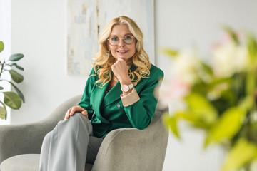 portrait of beautiful mature woman in eyeglasses smiling at camera Wall mural