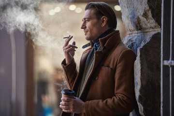 Side view pensive man smoking cigarette while tasting mug of appetizing coffee outdoor. Relax concept