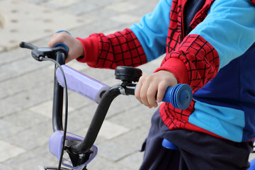 A boy on his bicycle, holding steering wheel