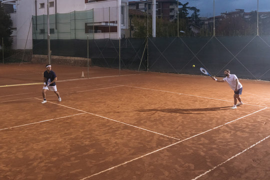 Group of friends play tennis a double match on a clay court