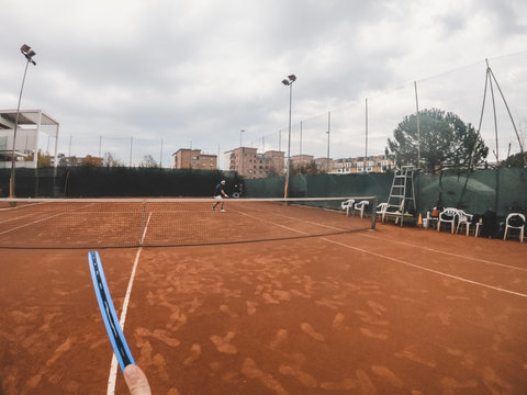 Point of view of tennis player during a match on a clay court