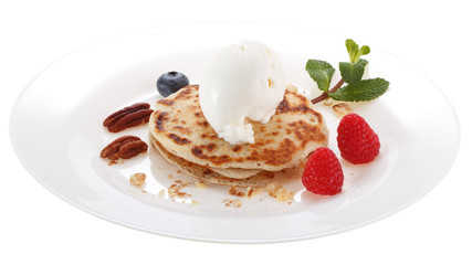 Serving pancakes with ice cream on the plate. Decorated with nuts, fresh berries and mint. Isolated on white background.