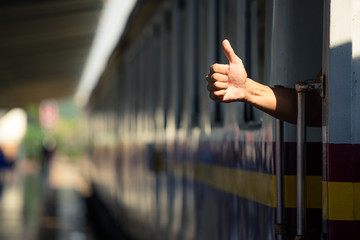close up view of a hand sign thumb up during departure of a train . departure