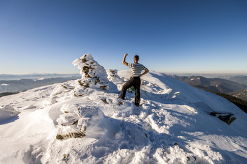 Man hiker on top of a mountain in winter