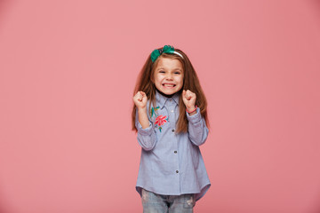 Smiling girl model in hair hoop and fashion clothes expressing happiness gesturing with clenched fists against pink background