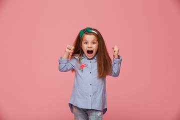 Beautiful female kid in hair hoop and fashion clothes clenching fists shouting with happiness and admiration against pink background