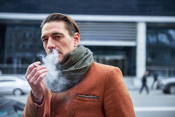 Portrait of calm man smoking cigarette while going on street. He looking at camera. Pleasure concept