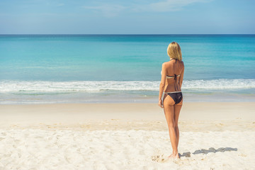 Young woman in bikini standing on the beach and enjoying blue sea. Back view.  Vacation and holiday on the beach concept.
