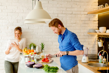 Young couple have fun in modern kitchen indoor while preparing vegetables food for lunch