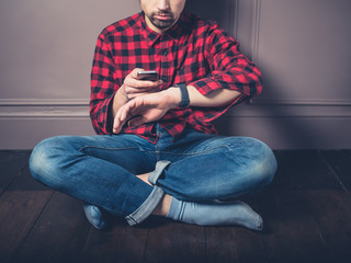 Young man on wooden floor with smart watch