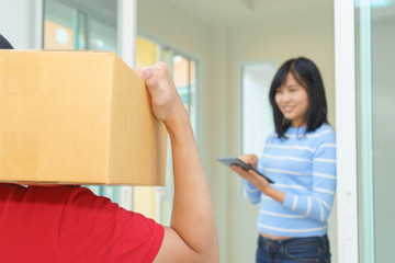Woman receiving package and signing on digital tablet from delivery man