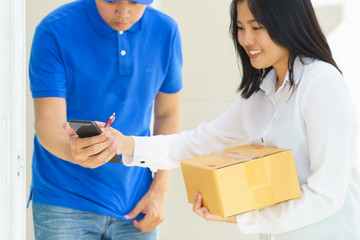 Delivery man pointing on smartphone and woman receiving package and signing on digital mobile phone
