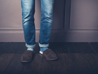 Young man with slippers on wooden floor