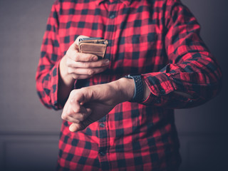 Man in flannel shirt with phone and smart watch