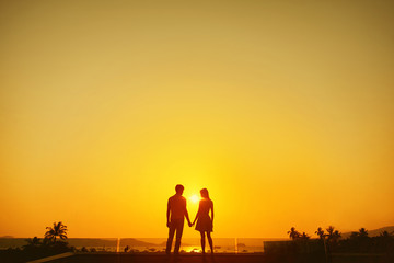 Silhouette of couple standing on the roof of building with view on bay and palms at sunset.