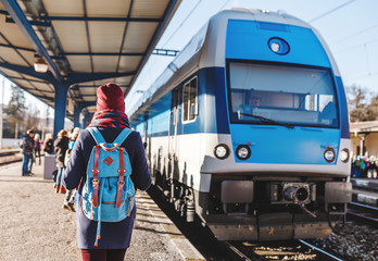 A young tourist girl with backpack waits train on railway station