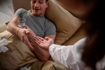 Here you are. Sick man lying in bed and holding a glass of water with smile. Woman is giving him pill. Focus on male and female hands