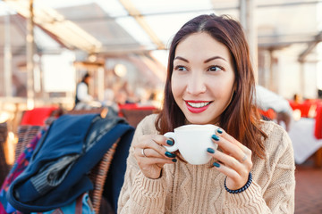 Young pretty eastern woman in cafe drinking coffee
