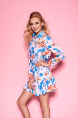 Fashionable beautiful woman in nice dress. Fashion spring summer photo. Pink background