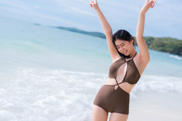 Beautiful young Asian woman in bikini at the beach Free woman enjoying freedom feeling happy at beach happy. Beautiful serene relaxing woman in pure happiness and elated enjoyment with arms raised