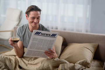 Waist up portrait of happy guy reading the newspaper. He is holding a cup of coffee and sitting in bedroom. Copy space in right side