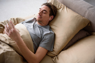 Tranquil adult male lying on bed and looking at the phone with peace. He is listening to music while using headphones