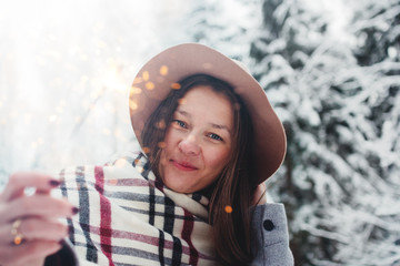 Stylish woman wearing hat and scarf hold bengal light close-up in hand and walking among snowy forest. Female hipster having fun and enjoying sparkler fire in winter holidays