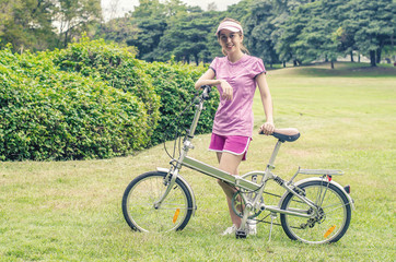 Vintage beautiful fashion girl with bicycle in the park