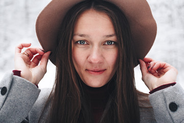 Face of a beautiful and cute woman close-up in vintage hat on background winter view