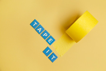 Adhesive tape roll on yellow background