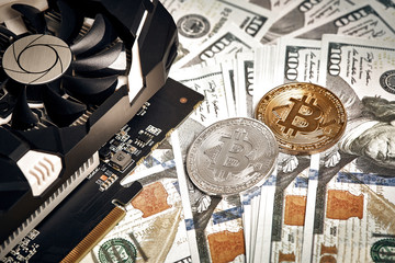 The coins of bitcoin lies on dollars with video card. Exchange bitcoin cash for a dollar