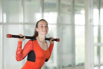 Charming young girl in sport suit doing sit-ups with barbell during workout in the gym
