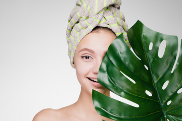 cute smiling girl with a towel on her head holding a green leaf, day spa