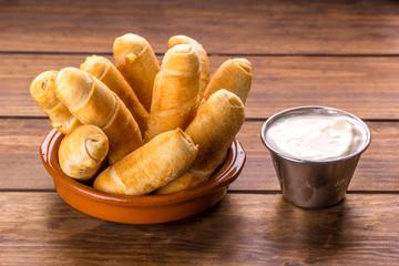 Tequeños, Typical Venezuelan snack with garlic sauce on a wood background