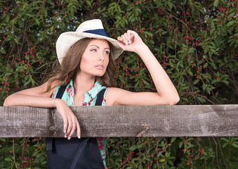 Portrait of a young attractive woman near a wooden fence. Hat and stylish clothes