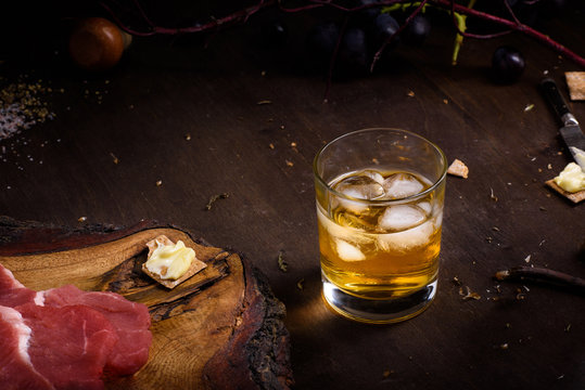 Raw meat, beef steak on wooden table, a glass of whiskey.