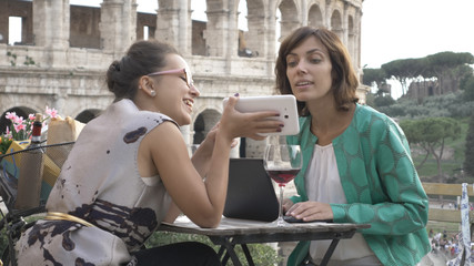 Two happy young woman tourists sitting at the table of a bar restaurant in front of the Colosseum in Rome using smartphone and laptop computer while having a glass of italian red wine. Stylish