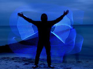 Silhouette eines Mannes am Strand mit Lichtmalerei
