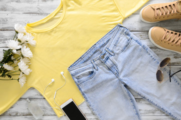 Womens fashion clothing, shoes, accessories (beige leather sneakers, blue jeans, yellow top (t-shirt) headphones, cell phone, perfume, sunglasses. Fashion. View above. Spring summer collection