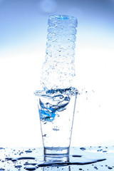 Empty bottle in glass of water with splashing and reflection.