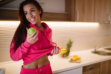 Fit sporty girl eating apple at kitchen and looking through window.
