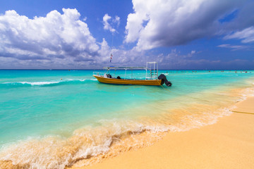 Yellow speedboat on the beach of Caribbean Sea in Mexico.