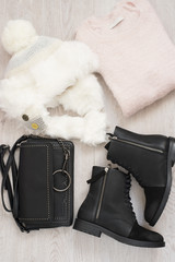 Women trendy fashion clothes collage with sweaters, white fur hat, boots and bag. Flat lay