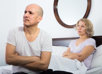 Mature couple having quarrel in bedroom.