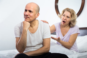 Mature couple sorting out relationships in bed.