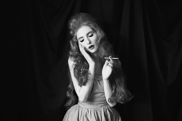 A smoking woman with pale skin and long curly red hair in a pink dress on a black background. Beautiful girl with red lips with a cigarette in her hands. Beauty makeup. Redhead model. Sensual portrait