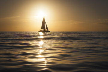 Silhouette of sailboat at shimmering golden sunset on Gulf of Mexico