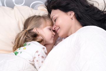 Mom and little daughter are lying in bed with their eyes closed nose to nose