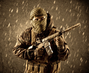 Dangerous heavily armed terrorist soldier with mask on grungy rainy background